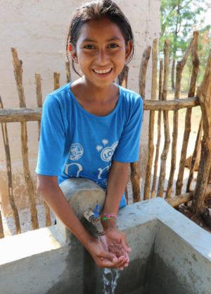 girl at pila in Zapote, Honduras 4x6